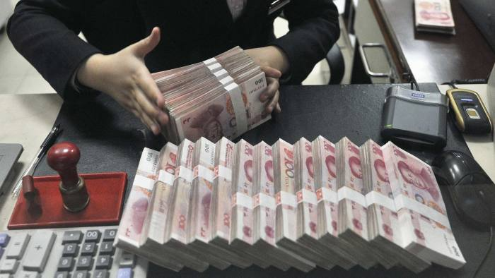 A clerk arranges bundles of 100 Chinese yuan banknotes at a branch of China Merchants Bank in Hefei...A clerk arranges bundles of 100 Chinese yuan banknotes at a branch of China Merchants Bank in Hefei, Anhui province March 17, 2014. China's yuan eased against the dollar on Monday after the central bank doubled the currency's daily trading band as part of its commitment to let markets play a greater role in the economy. REUTERS/Stringer (CHINA - Tags: BUSINESS POLITICS)