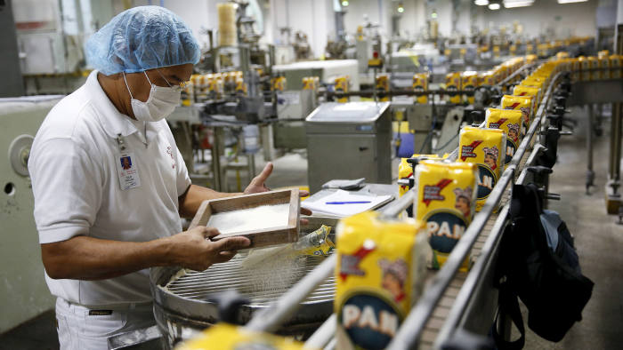 A worker inspects a sample on the production line of PAN corn flour at an industrial complex of food company Empresas Polar in Turmero, in the state of Aragua, Venezuela, October 23, 2015.