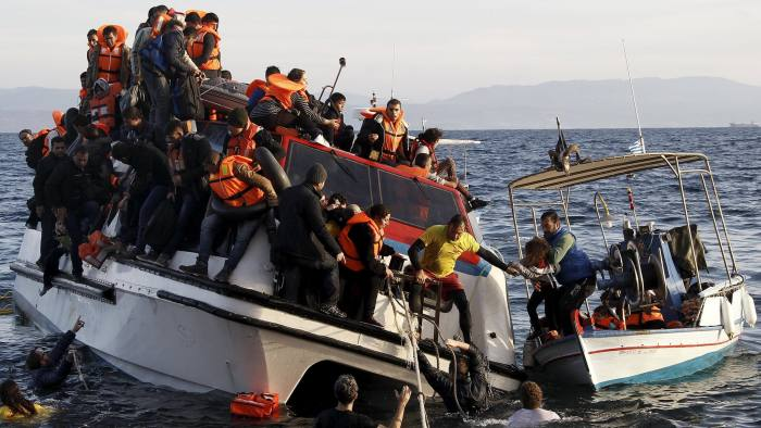 A Greek fishing boat (R) evacuates people from a half-sunken catamaran carrying around 150 refugees, most of them Syrians arriving after crossing part of the Aegean sea from Turkey, on the Greek island of Lesbos, October 30, 2015. There were no casaulties amongst the refugees who were travelling on the catamaran, according to a Reuters witness. The death toll from drownings at sea has mounted recently as weather in the Aegean has taken a turn for the worse, turning wind-whipped sea corridors into deadly passages for thousands of refugees crossing from Turkey to Greece. REUTERS/Giorgos Moutafis