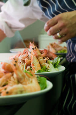 An image of a man preparing several dishes of langoustines and king prawns
