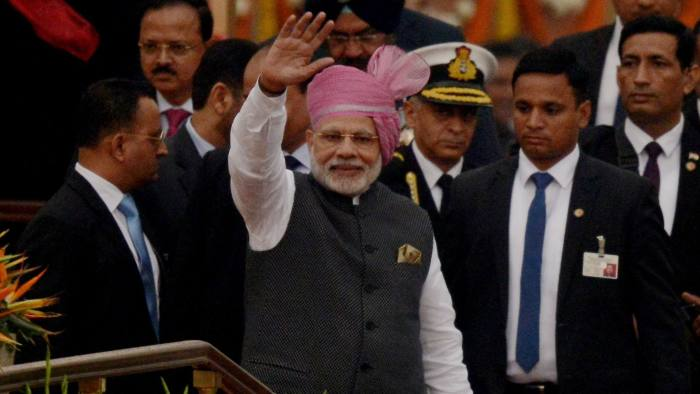 Indian Prime Minister Narendra Modi waves to the crowd during the 68th Republic Day parade in New Delhi on January 26, 2017. Motorbike stunt riders and herds of camels wowed the crowds gathered in the centre of New Delhi January 26 to celebrate Republic Day, an annual showcase of India's military hardware and cultural diversity. After the presidents of the United States and France attended the last two extravaganzas, the Crown Prince of Abu Dhabi Mohammed bin Zayed Al Nahyan was this year's chief guest as everyone from elite troops to schoolchildren paraded down the landmark Rajpath boulevard. / AFP / Money SHARMA (Photo credit should read MONEY SHARMA/AFP/Getty Images)