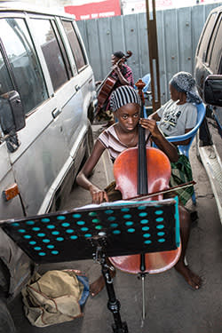 Cellists practise between parked cars at the Kimbanguist Symphony Orchestra headquarters, Kinshasa