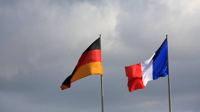 The national flag of Germany, left, and the national flag of France fly outside the Chancellery in Berlin, Germany, on Monday, Sept. 22, 2014. German Chancellor Angela Merkel hosts Valls in Berlin today as France bridles at demands to narrow its budget deficit in a stagnant economy. Photographer: Krisztian Bocsi/Bloomberg
