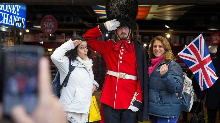 Tourists pose together for a picture with a man in a Guardsman's uniform in central London on January 16, 2017. Prime Minister Theresa May won endorsement from US President-elect Donald Trump over her Brexit course but sterling plunged on Monday on fears that Britain could be on a collision course with its EU allies. / AFP / Daniel LEAL-OLIVAS (Photo credit should read DANIEL LEAL-OLIVAS/AFP/Getty Images)