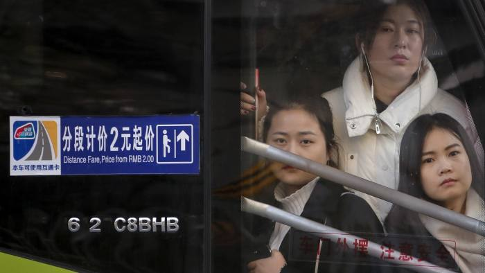 Chinese women look out of a window of a crowded bus traveling from the outskirts of the capital city clogged in heavy traffic on a road during the morning rush hour in Beijing, Tuesday, Nov. 28, 2017. The Beijing city government said last year it plans to cut by 15 percent the total population of the city and limit it to 23 million by 2020. (AP Photo/Andy Wong)