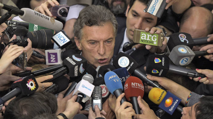 """Buenos Aires Mayor and presidential candidate for """"Cambiemos"""" party Mauricio Macri (C) is hounded by the media after voting in Buenos Aires on October 25, 2015"""