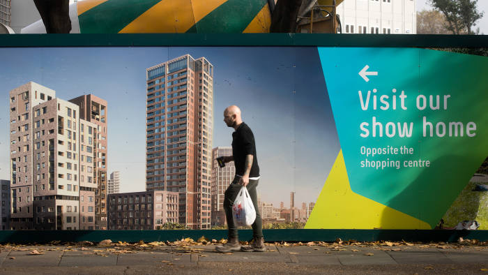 A pedestrian walks past a hoarding advertising a block of flats, currently under construction, in London, U.K., on Monday, Oct. 31, 2016. London property prices are set to fall next year as uncertainty about Britain's exit from the European Union damps the U.K. housing market, according to the Centre for Economics and Business Research. Photographer: Simon Dawson/Bloomberg