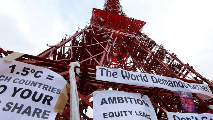 """Placards which read """"1.5 Degrees Celsius = rich countries do your fair share"""" and """"the World demands better"""" are seen on a replica of the Eiffel Tower during the World Climate Change Conference 2015 (COP21) in Le Bourget, near Paris, France, December 11, 2015. REUTERS/Jacky Naegelen"""