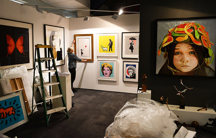 Ann Marie Gormley hangs a print by artist Banksy, at the press preview for the London Art Fair in Islington, ahead of its opening to the public tomorrow. PRESS ASSOCIATION Photo. Picture date: Tuesday January 16, 2018. See PA story ARTS London. Photo credit should read: John Stillwell/PA Wire