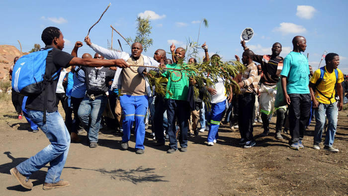 Striking Lonmin mine workers dance and sing while starting to gather next to a hill called Wonderkop on May 14, 2013 in Marikana, where 34 people were shot and killed by South African police during protest action over better wages on August 16, 2012. Thousands of mine workers downed tools today at South Africa's restive Lonmin mine after a union leader was shot dead in the restive platinum belt at the weekend. Work has stopped at all of the firm's 13 shafts in the northwestern Rustenburg mining town, the world's top platinum producing region.