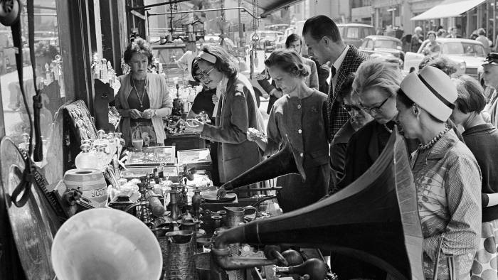 People crowded around a stall outside a shop selling gramophones and other items