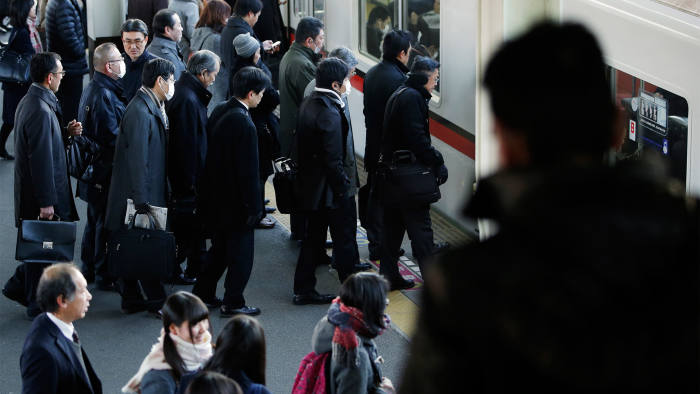 Morning commuters wait to board a train at a station in Inzai, Chiba Prefecture, Japan, on Tuesday, Dec. 9, 2014. Japan's recession was deeper than initially estimated as company investment unexpectedly shrank, a blow to Prime Minister Shinzo Abe as he campaigns for re-election on his economic credentials. Photographer: Kiyoshi Ota/Bloomberg