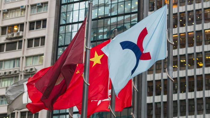 The flag (R) of the Hong Kong Exchanges and Clearing Limited (HKEX) is hoisted next to China's flag (C) in Hong Kong on August 16, 2016. China's central government has approved plans to link trading between the Shenzhen stock exchange and the Hong Kong market, it said on August 16, paving the way for the long-awaited reform. / AFP PHOTO / Anthony WALLACEANTHONY WALLACE/AFP/Getty Images