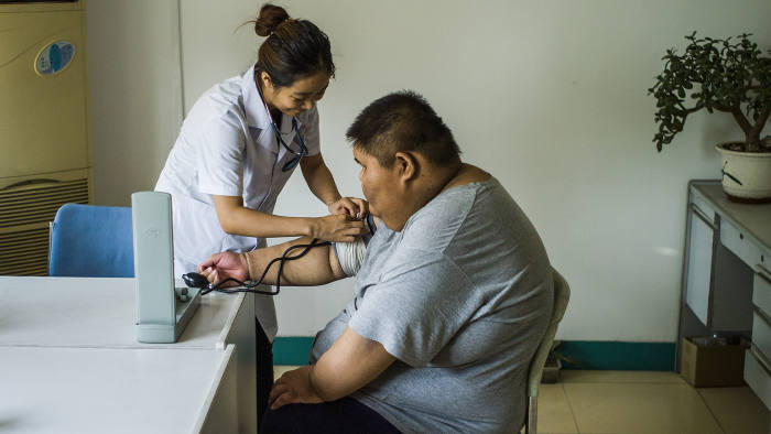 This picture taken on May 25, 2015 shows a nurse taking the blood pressure of an overweight boy during his acupuncture and exercise treatment at the Aimin (Love the People) Fat Reduction Hospital in the northern port city of Tianjin. AFP PHOTO / FRED DUFOUR (Photo credit should read FRED DUFOUR/AFP/Getty Images)