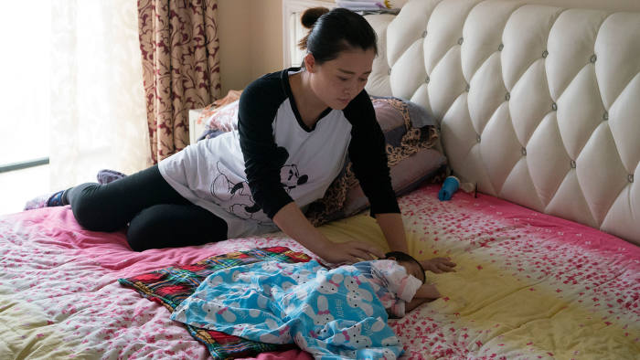 Safely delivered: Wan Xindi back at her home in Yichang with her newborn daughter Xiaozuo