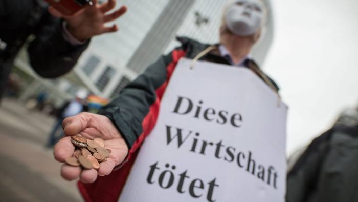 A demonstrator carries a sign that reads 'This economy kills' while throwing coins at the feet of Deutsche Bank shareholders at the entrance to the shareholders' meeting of the German financial services company in Frankfurt