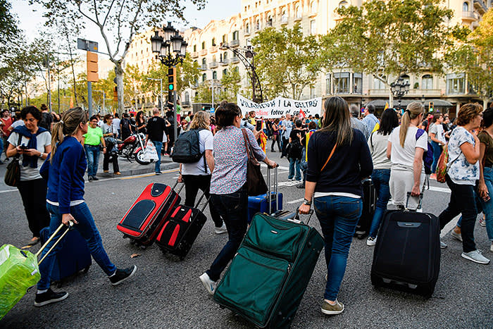 Tourists walk with their suitcases as protesters attend a demonstration called by the General Confederation of Labour (CGT) Catalan worker's union at Passeig de Gracia in Barcelona during a general strike in Catalonia on October 3, 2017. Large numbers of Catalans observe a general strike today to condemn police violence at a banned weekend referendum on independence, as Madrid comes under growing international pressure to resolve its worst political crisis in decades. / AFP PHOTO / LLUIS GENE (Photo credit should read LLUIS GENE/AFP/Getty Images)