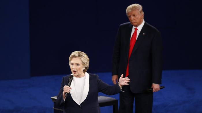 Hillary Clinton, 2016 Democratic presidential nominee, speaks as Donald Trump, 2016 Republican presidential nominee, stands during the second U.S. presidential debate at Washington University in St. Louis, Missouri, U.S., on Sunday, Oct. 9, 2016. As has become tradition, the second debate will resemble a town hall meeting, with the candidates free to sit or roam the stage instead of standing behind podiums, while members of the audience -- uncommitted voters, screened by the Gallup Organization -- will ask half the questions. Photographer: Andrew Harrer/Bloomberg