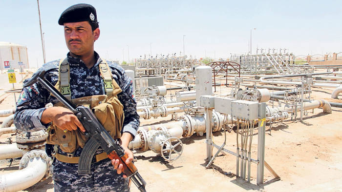 A member from the oil police force stands guard at Zubair oilfield in Basra, southeast of Baghdad June 18, 2014