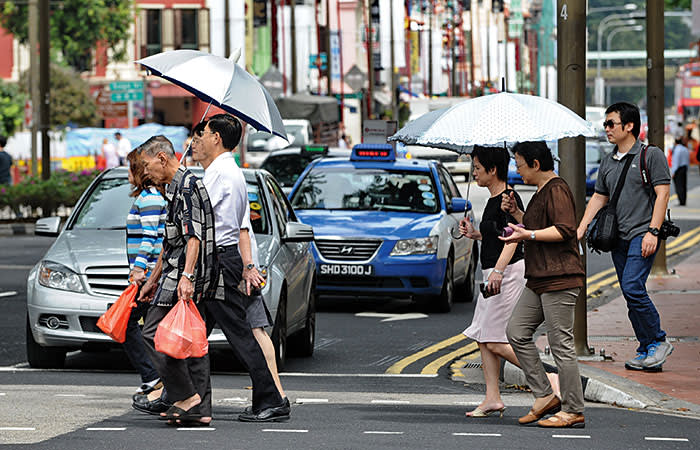 Pedestrians cross a street in Singapore on January 2, 2013