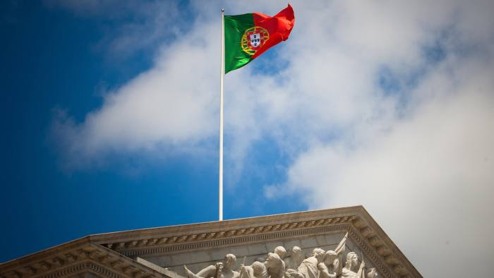 A Portuguese national flag flies above the parliament building in Lisbon, Portugal, on Wednesday, July 6, 2011. Portugal's downgrade to junk status and wrangling over the role of investors in a new Greek bailout package fueled concern about the solvency of the region's high-debt nations, sending their bonds tumbling. Photographer: Mario Proenca/Bloomberg