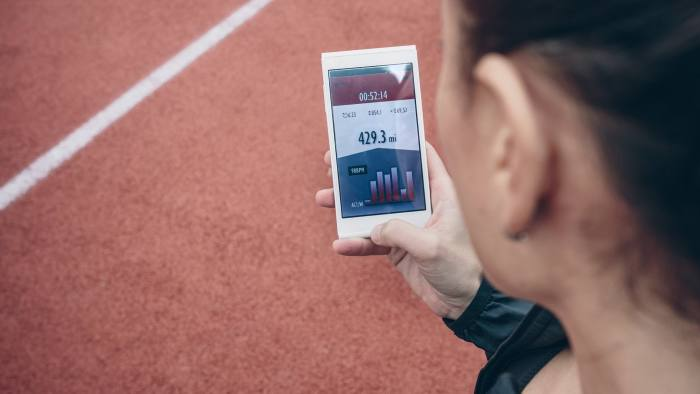 Spain, Asturias, Back view of brunette woman looking smartphone with training data on screen over running track background
