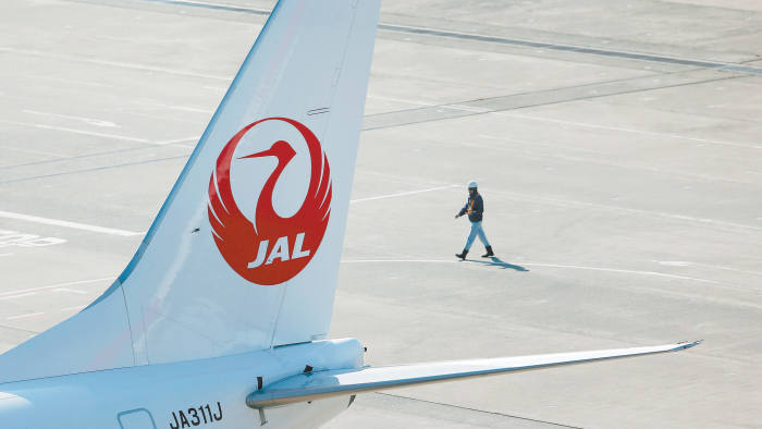 An airport staff member walks next to a Japan Airlines aircraft at Haneda Airport in Tokyo February 4, 2013