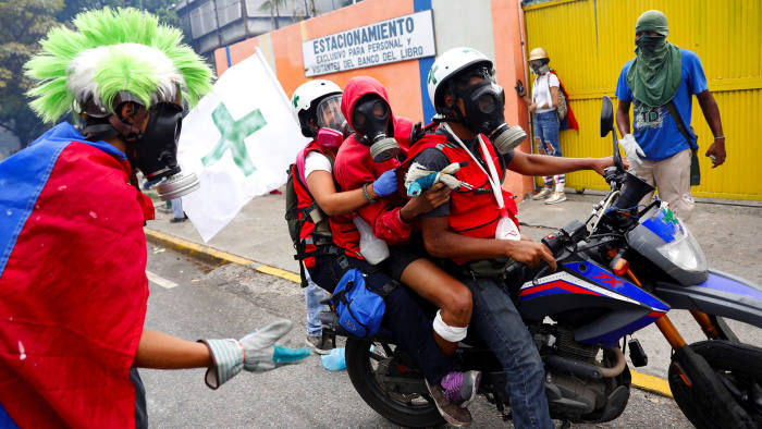 An injured demonstrator is helped by volunteer members of a primary care response team during a rally against Venezuela's President Nicolas Maduro in Caracas, Venezuela June 5, 2017. REUTERS/Carlos Garcia Rawlins TPX IMAGES OF THE DAY - RTX395M7