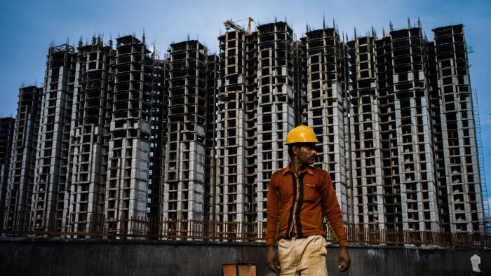 A construction worker stands on the construction site of a housing block in Sector 105 of Noida, in Uttar Pradesh, India
