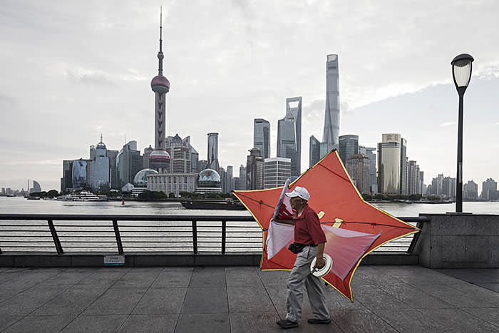 A man carries a kite along the bund as the Lujiazui Financial District stands in the background in Shanghai, China, on Monday, Sept. 4, 2017.