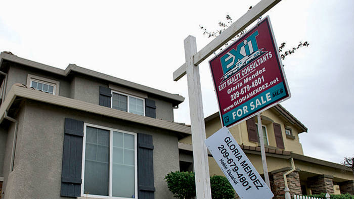 An Exit Realty Consultants 'for sale' sign is displayed in front of a house in Stockton California, US