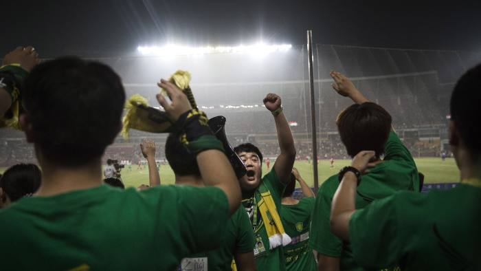 CHINA OUT BEIJING, CHINA - JUNE 28: Ultra supporters and fans of the Beijing Guoan FC chant slogans during a match against Chongcing Lifan FC in Chinese Super League play on June 28, 2015 in Beijing, China. There are growing legions of ardent supporters and fans of China's football clubs. The government is also trying to foster a football culture in the country by mandating football programs in 20,000 Chinese schools in a recent plan devised by President Xi Jinping to make China a football power. (Photo by Kevin Frayer/Getty Images)
