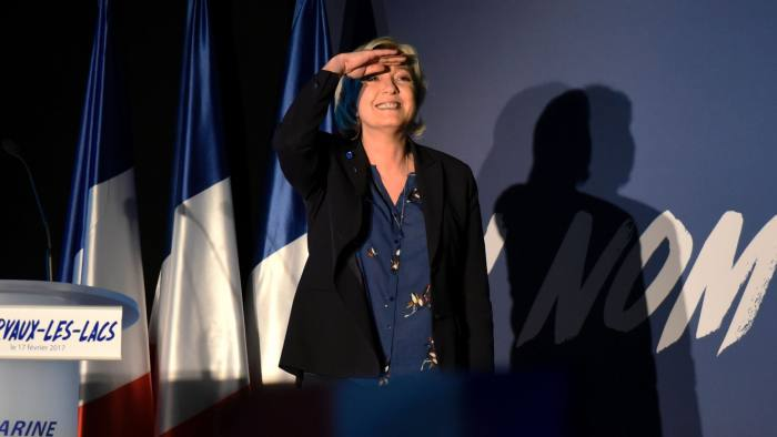 French presidential election candidate for the far-right Front National (FN) party Marine Le Pen gestures as she speaks during a public meeting, on February 17, 2017, in Clairvaux-les-Lacs, central eastern France. The slogan reads