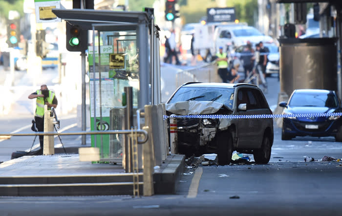 """TOPSHOT - A white SUV (C) sits in the middle of the road as police and emergency personnel work at the scene of where a car ran over pedestrians in Flinders Street in Melbourne on December 21, 2017. The car ploughed into a crowd in Australia's second-largest city on December 21 in what police said was a """"deliberate act"""" that left more than a dozen people injured, some of them seriously. / AFP PHOTO / Mal FaircloughMAL FAIRCLOUGH/AFP/Getty Images"""