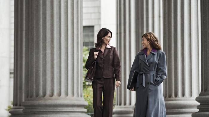 Two women walking in front of courthouse talking having a conversation