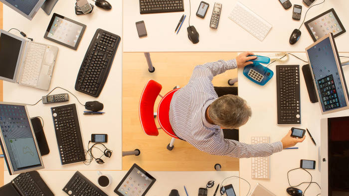 Man surrounded by desks and computers