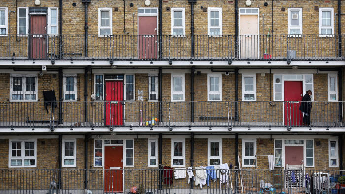 A woman looks out from a residential development in the London borough of Tower Hamlets on February 21, 2013 in London, England