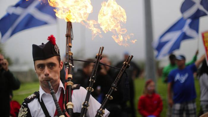 Piper, Ryan Randall, leads a march to the polling station in Craigmillar, Edinburgh.