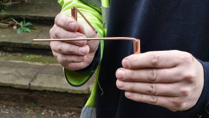 EHF85C A water engineer uses copper divining rods to trace the course of an underground pipe (UK), a practice known as dowsing