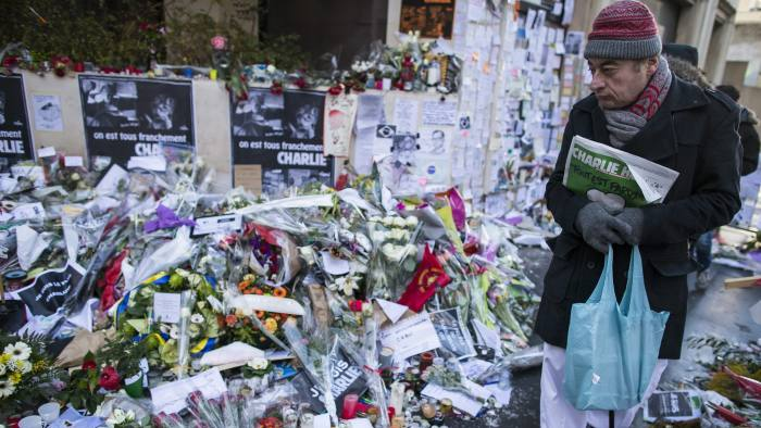epa04559462 A man holding the new edition of the French satirical magazine Charlie Hebdo pays his respects in front of the improvised memorial on Rue Nicolas Appert, near the Charlie Hebdo headquarters, site of the 07 January attack in which 12 of the newspaper's staff were killed by two gunmen, in Paris, France, 14 January 2015. Charlie Hebdo, attacked by gunmen on 07 January, features cartoons of the prophet Muhammad in its edition, and it is published on 14 January. It will have a print run of three million, media reports said, up from an earlier announced run of one million; and far in excess of the weekly magazine's usual circulation of 60,000. EPA/IAN LANGSDON