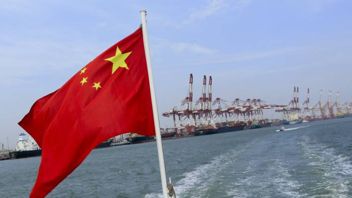 A Chinese flag flies on a vessel moving past the Tianjin Port (Group) Co. Ltd. docks in Tianjin, China, on Wednesday, Sept. 12, 2012. The Chinese government is trying to meet a 7.5 percent economic growth target set in March, which would already be the weakest expansion since 1990. Photographer: Nelson Ching/Bloomberg