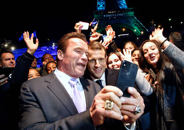 TOPSHOT - Former Governor of California and US actor Arnold Schwarzenegger (L) and French President Emmanuel Macron (C) take a selfie with youths in front of the Eiffel Tower illuminated in green, aboard a boat cruising on the river Seine, after the One Planet Summit in Paris on December 12, 2017. The French President hosts 50 world leaders for the
