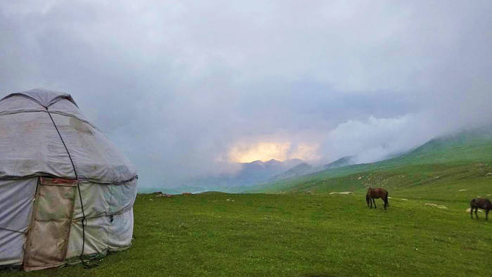 Robin's yurt and horses grazing under clearer skies after a dramatic rain storm