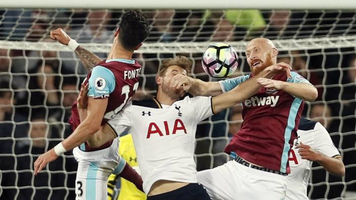 Tottenham's Harry Kane, center, battles for the ball with West Ham's James Collins during the English Premier League soccer match between West Ham United and Tottenham Hotspur at the London Stadium in London, Friday, May 5, 2017. (AP Photo/Kirsty Wigglesworth)