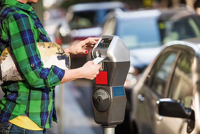 Unknown female paying fee to parking meter.