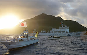 Japanese and Chinese boats sail past one of the disputed Senkaku/Diaoyu islands last year