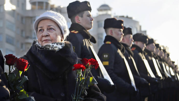 Women with flowers stand next to Belarusian military cadets holding portraits of soldiers who were killed during the Soviet war in Afghanistan, during a ceremony at memorial on the Island of Tears in Minsk, Wednesday, Feb. 15, 2017. The ceremony was held to mark the 28th anniversary of the Soviet pullout from Afghanistan. (AP Photo/Sergei Grits)