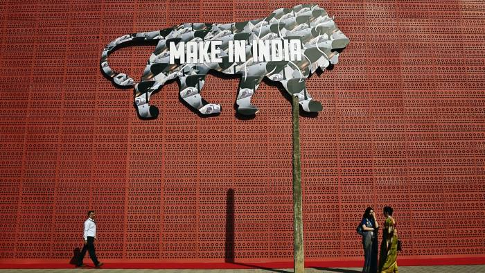 Indian participants stand near a wall bearing the image of the mascot during the opening of the 'Make in India Week' in Mumbai on February 13, 2016. Over 190 companies, and 5,000 delegates from 60 countries, are taking part in the first 'Make in India Week' to be held in Mumbai from February 13-18. AFP PHOTO / PUNIT PARANJPE / AFP / PUNIT PARANJPE        (Photo credit should read PUNIT PARANJPE/AFP/Getty Images)