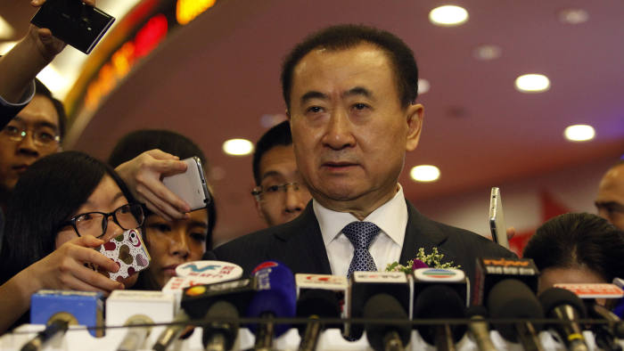 In this file photo taken on on December 23, 2014, Wang Jianlin, CEO of Dalian Wanda Commercial Properties Co. speaks at a press conference during the company's IPO at the Hong Kong stock exchange. China's richest man, Wang Jianlin, has built a 100 billion USD business empire founded on shopping malls, but now he has set his eyes on a new trophy -- building a global sports conglomerate to match his country's economic and political might. Isaac Lawrence / AFP