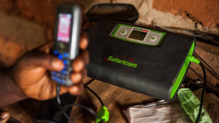 Rebecca Wambua, holds a mobile phone charging at a Safaricom electrical unit using M-Kopa solar technology in Ndela village, Machakos country, Kenya, on Wednesday, July 22, 2015. Customers agree to pay for the solar panel with regular instalments which M-Kopa, a Nairobi-based provider of solar-lighting systems, then monitors for payments that are made using a mobile-phone money-transfer service. Photographer: Waldo Swiegers/Bloomberg